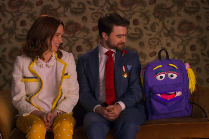 UNBREAKABLE KIMMY SCHMIDT KIMMY VS. THE REVEREND (L TO R) ELLIE KEMPER as KIMMY SCHMIDT, DANIEL RADCLIFFE as FREDERICK, and JAN THE BACKPACK in UNBREAKABLE KIMMY SCHMIDT KIMMY VS. THE REVEREND Cr. Courtesy of Netflix © 2020